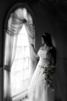 Bride looks out the window before her wedding photography really begins