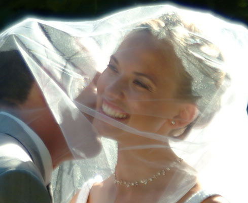 Bride gets a kiss under her veil after her los angeles wedding photography