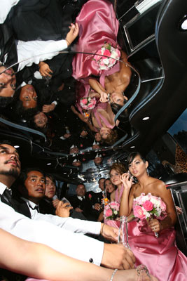 Groomsmen and bridesmaids enjoy the trip to the reception in their limosine