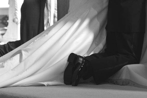 Detail shot of the groom's feet and the brides dress as they kneel at the alter.